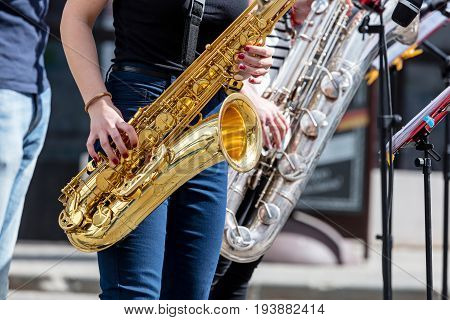 Young Saxophonists Playing Saxes During Street Performance
