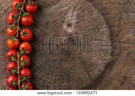 Top view of a bunch of cherry tomato Ripe natural tomatoes on a branch on wooden background with copy space Ripe tomatoes ready to eat Farm of tasty red tomatoes.