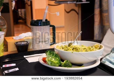 Bowl of penne pasta with pesto on a tray in a hospital