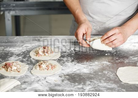Selective focus. the Baker forms his own hands the billet of dough for baking. billet bun of dough with filling inside. manufacturing of food products. Baker lays out the filling on the workpiece. hands closeup. the concept for the site bakery.