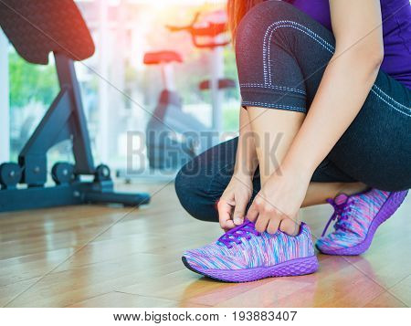 Running shoes - closeup of woman tying shoe laces. Female sport fitness runner getting ready for jogging in gym room with fitness equipments in backgroound