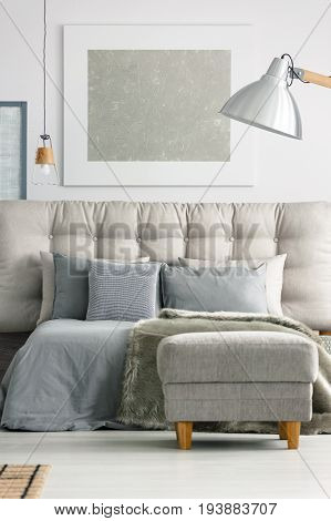 Ottoman by the grey comfortable bed in modern white bedroom
