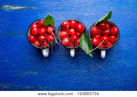 Cherry In Enamel Cup On Blue Wooden Background. Healthy, Summer Fruit. Cherries. Top View. Copy Spac