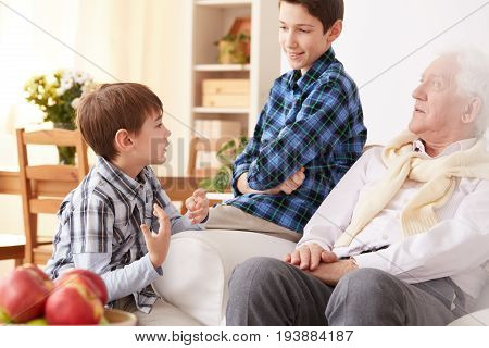 Lovely grandfather talking with young grandsons in cozy living room