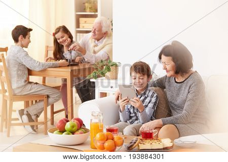 Young grandson showing tablet to his happy grandmother