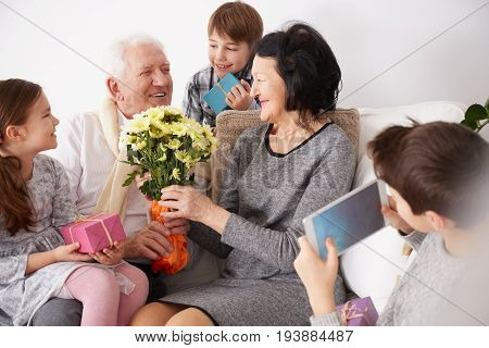 Happy grandparents receiving flowers and presents from their lovely grandchildren