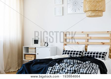 Modern design of cozy bedroom in black and white colors