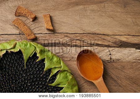 Sunflower with seed sunflower oil in spoon and Bread crumbs on wooden rustic board. Top view copy space. Diet and healthy eating concept.