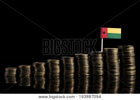 Guinea Bissau Flag With Lot Of Coins Isolated On Black Background