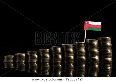 Omani Flag With Lot Of Coins Isolated On Black Background