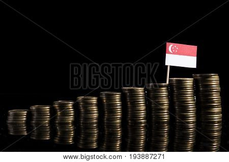 Singaporean Flag With Lot Of Coins Isolated On Black Background