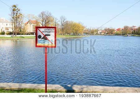 A Sign To Swim Is Forbidden On The Shore Of A Lake In A City Park In Russia. Text In Russian Languag