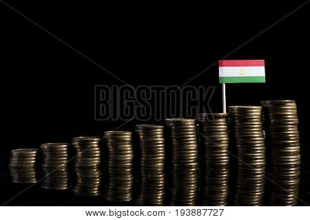 Tajikistan Flag With Lot Of Coins Isolated On Black Background