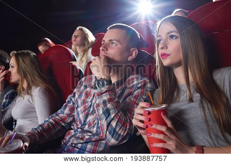 Young man and woman enjoying a movie at the cinema together couples dating entertainment premiere activity concept.