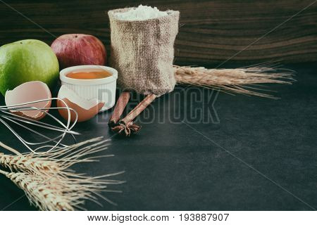 Bakery background comprise with apples wheat flour egg and cinnamon on granite table with copy space.Prepare ingredient for baking apple cake on granite background. Bakery background concept.