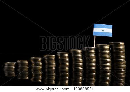 Nicaraguan Flag With Lot Of Coins Isolated On Black Background