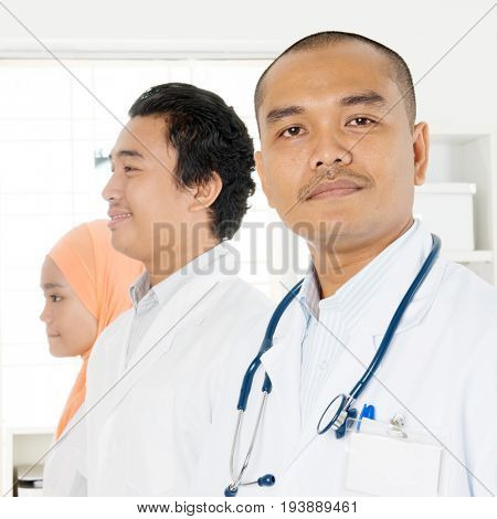 Portrait of medical team at hospital office, Southeast Asian Muslim doctors and nurses.
