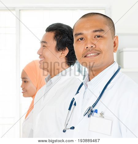 Clinic, profession, people, health care and medicine concept - happy group of Southeast Asian medics or doctors at hospital.