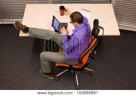 multitasking & healthy lifestyle in office  - man working with tablet, holding mug, stretching leg,