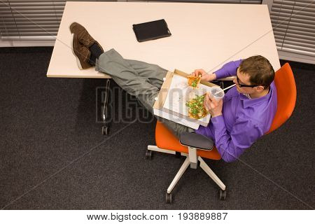 fast meal in office - man heaving break for pizza