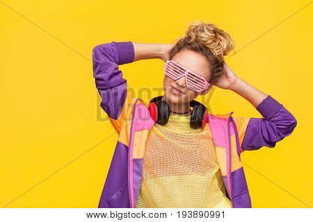Blonde woman with hair bun wearing shutter glasses and purple jacket posing standing against yellow background.
