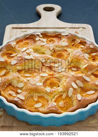 Apricot tart in a bright blue cake pan, placed on a wooden chopping board