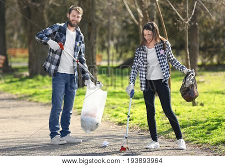 Young volunteers picking up litter in park