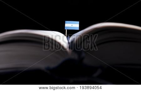 Nicaraguan Flag In The Middle Of The Book. Knowledge And Education Concept.