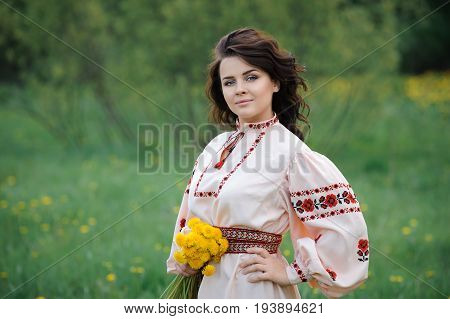 Portrait of a beautiful girl in Slavic clothes with a bouquet of dandelions. Summertime