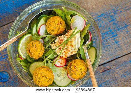 Vegetarian green salad with falafel and hummus. Love for a healthy vegan food concept.