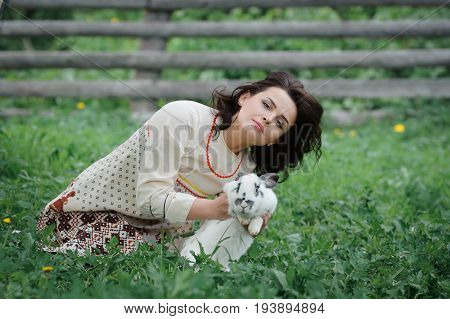 Portrait of a beautiful girl in Slavic clothes. Young woman with a rabbit. Summertime