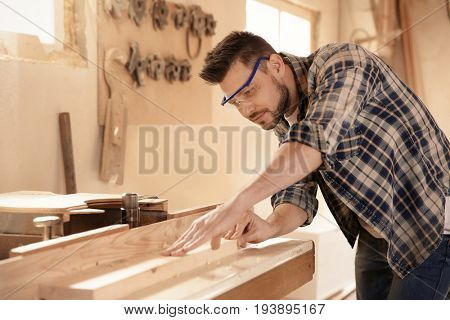 Carpenter working with timber strip in shop