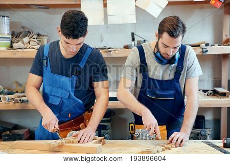 Young carpenters with chisels in workshop