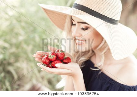 Smiling blonde woman 24-26 year old holding strawberry outdoors. Wearing straw hat. Healthy eating.