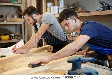 Two young carpenters working in shop