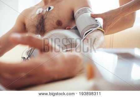 A nurse fastens the tonometer cuffs on the patient's arm