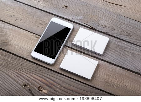Business Cards And Smartphone Isolated On Old Wood Background