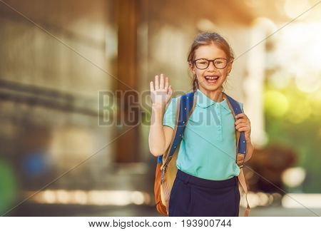 Pupil of primary school. Girl with backpack near building outdoors. Beginning of lessons. First day of fall.