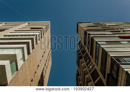 Low angle view of generic apartment buildings, with blue sky in the background.