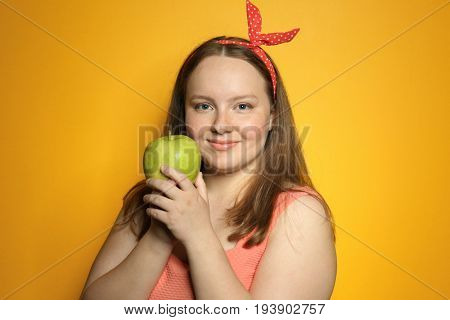 Overweight young woman with apple on color background. Diet concept