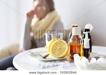 Medicines and lemons with blurred ill woman on background