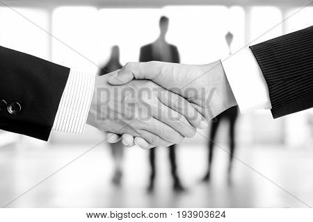 Handshake of businessmen on blur businesspeople background monochrome effect - greeting dealing merger and a acquisition concepts