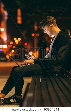 Young man work and communicate at night, free space. Student working on his computer in park in night time. Smiling guy searching information at place with free wi-fi