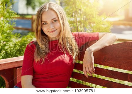 Pleasant-looking Blonde Female Wearing Casual Red Sweater Sitting At Comfortable Wooden Bench Agains