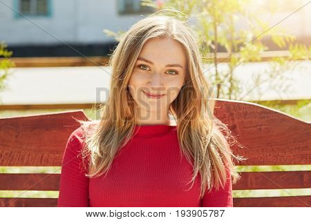 Outdoor Portrait Of Pretty Woman With Light Hair, Freckles And Blue Eyes Sitting On Wooden Bench In