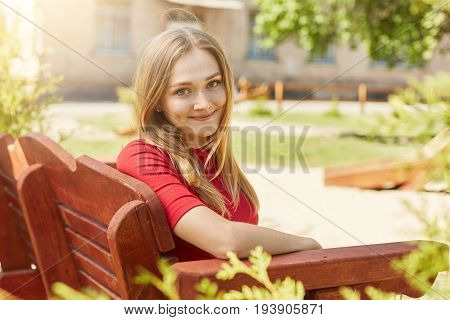 Sideways Portrait Of Beautiful Female With Blonde Hair, Smiling Into Camera Having Dimples On Cheeks