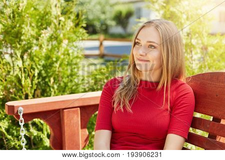 Outdoor Portrait Of Pretty Female With Straight Fair Hair And Pleasant Appearance Wearing Red Sweate