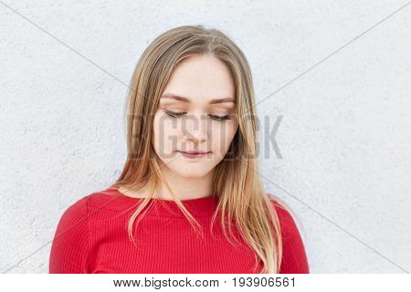 Adorable Blonde Woman In Red Dress Looking Thoughtfully Down Thinking Over Her Relationships With Bo