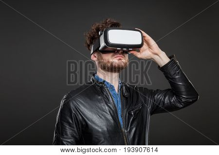 Man in a black leatherjacket wearing virtual reality goggles
