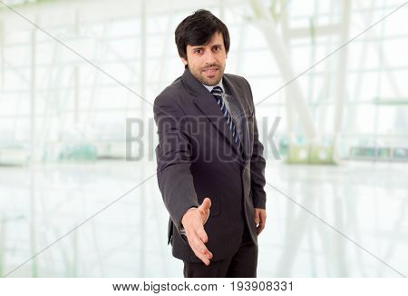 businessman in suit offering to shake the hand, at the office
